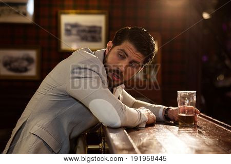 Young drunk man sitting at the counter in a pub or a bar and drinking beer