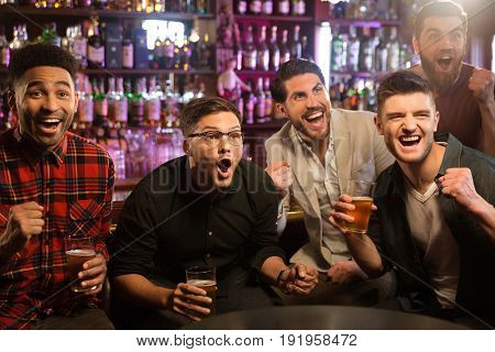 Happy friends having fun in pub by watching sport on TV together while drinking beer and cheering for team