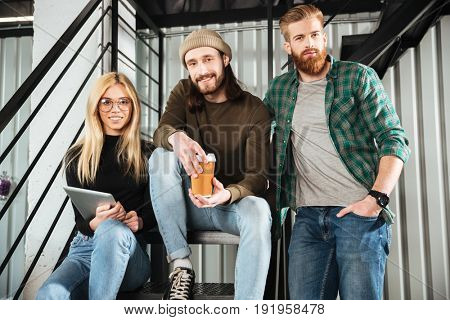 Image of young smiling colleagues in office sitting on ladder. Looking at camera.