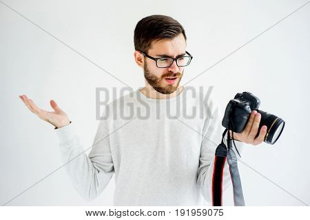 Portrait of a puzzled male photographer with digital camera