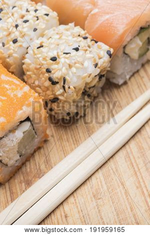 Sushi rolls with salmon sesame red caviar and sushi sticks lie on a light wooden board close-up view