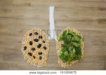 Overhead symbolic shot of human lungs made of dry peas and green leaves. Lung cancer tumor air environment pollution smoking concept. Clean air protection issue.
