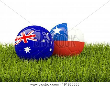 Two Footballs With Flags Of Australia And Chile On Green Grass
