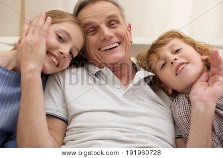 Love is everywhere. Cheerful smiling handsome man sharing a happy moment and expressing his love while his kids visiting him on the weekend
