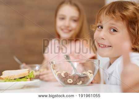Great taste. Lovely energetic sincere boy sitting at the table and eating sweet cereal while showing how much he enjoying it
