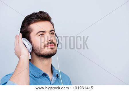 Dreamy Young Cute Guy Is Looking Up Imagining Something Nice. He Is Listening To The Music In White