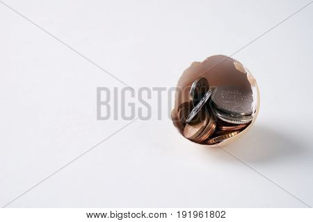 New money growing from a new cracked egg isolated on a white background with copy space. Concept which symbolizes a profitable business success fortune luck happiness.