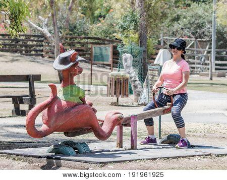 Young woman is riding on a kangaroo-shaped swing at the Australian Zoo Gan Guru in Kibbutz Nir David in Israel