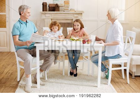 Lovely family gathering. Vibrant positive active siblings sitting at the table and eating sweet cereal their grandma cooking them in the morning