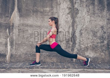 Pretty Young Slim Trainer Is Stretching Her Legs By Doing Exercise. She Is Training Outdoors On A Su