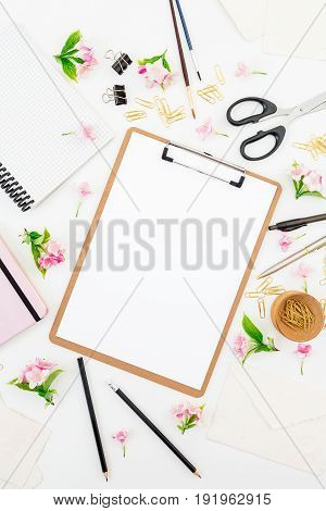 Freelancer or blogger desk with clipboard, notebook, pink flowers and accessories on white background. Lifestyle concept. Flat lay, top view.