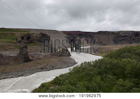 Iceland River Landscape On A Gray Cloudy Day. River Surrounded By Big Cliffs. Volcanic Rock Formatio