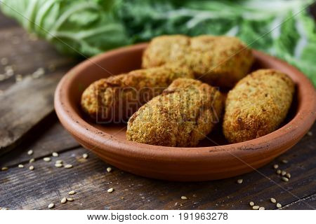 closeup of an earthenware plate with some homemade croquetas, spanish croquettes, on a rustic wooden table