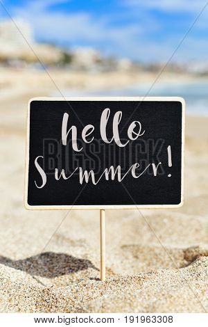 closeup of a black signboard with the text hello summer on the sand of a lonely beach