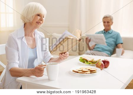 Lifelong hobby. Imaginative vibrant pretty woman reading a fascinating book she not giving up even when having a breakfast