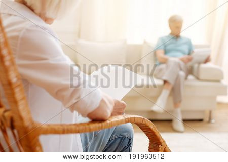 Important message. Relaxed attentive senior lady sitting in a chair and perusing a sheet of paper while enjoying a morning with her husband
