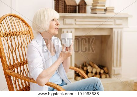 Warmth of home. Elegant stunning elderly lady sitting in a chair and enjoying a quiet and cozy atmosphere while spending time at home