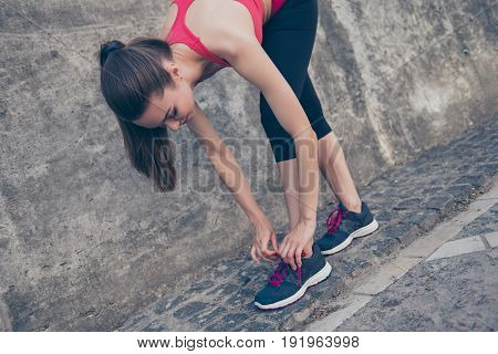 Young Sporty Woman Is Tying Laces Of Running Shoes Before Training Outdoors, In A Fashionable Sport