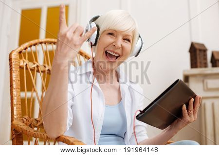 Aged rocker. Cute enthusiastic expressive lady being rather emotional while listening to some music using her tablet
