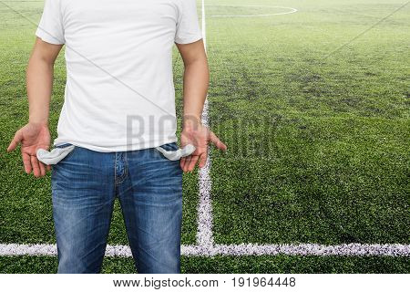 Man showing his empty pockets on soccer stadium background.