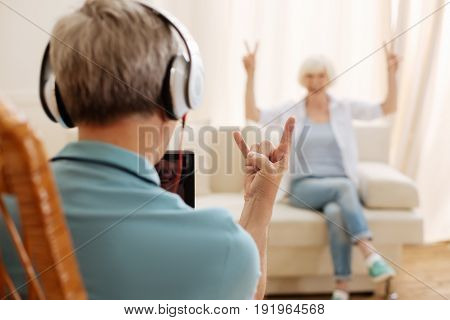 Forever young. Handsome cute hilarious gentleman wearing headphones and playing his playlist while having fun with his wife