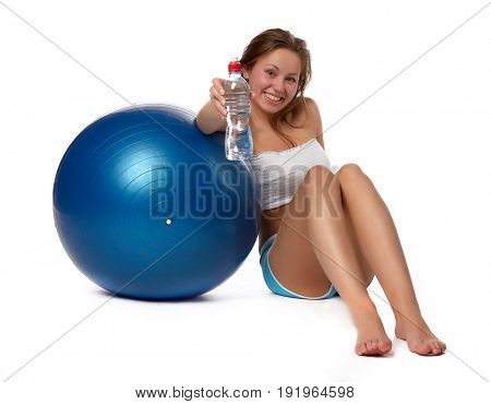 Young  beautiful woman with bottle of water and gymnastic ball on a white background.