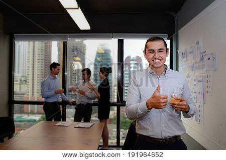 handsome businessman smile and showing thumbs up in the office business success concept