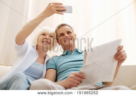 Capturing memories. Vibrant creative lively woman using the front camera for making a photo while memorizing a lovely morning with her husband