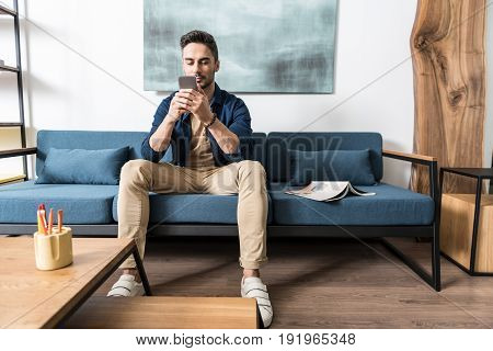 Portrait of serious young handsome man with beard is sitting on sofa inside cozy room and reading massage on his mobile phone. He is having rest