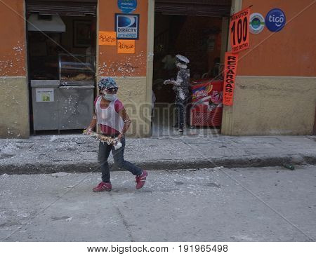 6TH JANUARY 2015 PASTO COLOMBIA - a little girl stalks the streets of Pasto with spray looking for her next victim celebrating at the Carnival de Blancos y Negros (Blacks and White Carnival) in Pasto in Colombia