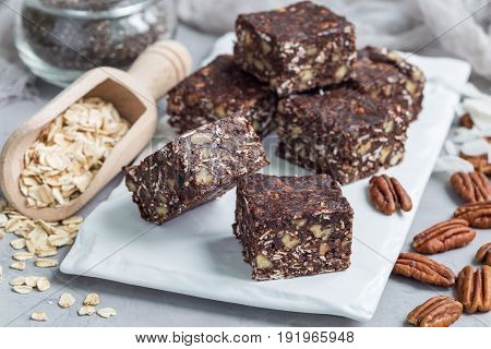 Paleo chocolate energy bars with rolled oats pecan nuts dates chia seeds and coconut flakes horizontal