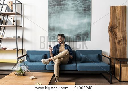 Cheery young man with beard is sitting on large sofa with magazine on laps and holding his smart phone in one hand. He is texting with somebody and smiling