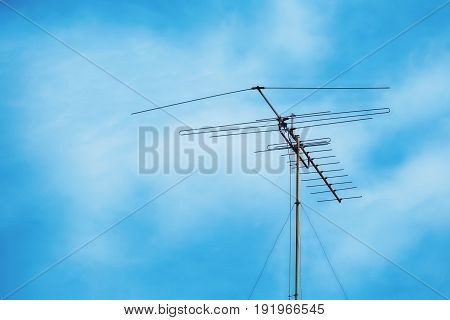 Television antenna on cloudy blue sky background