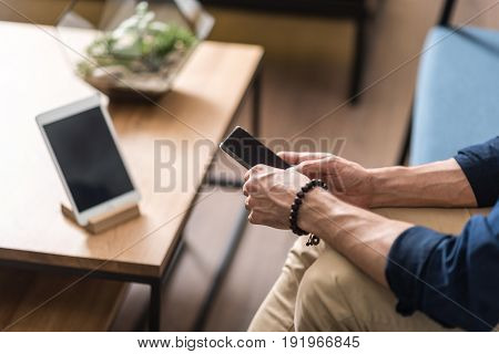 Close up of hands of young man holding smartphone. He is sitting on sofa near table with tablet lying on it. Focus on cellphone