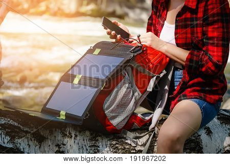 Woman Using Smartphone On The River. Charges Using Solar Panels.