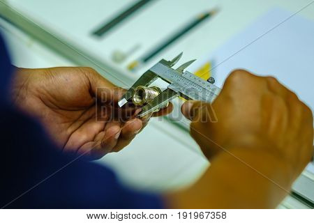 Man's hands using Vernier caliper to measure the object