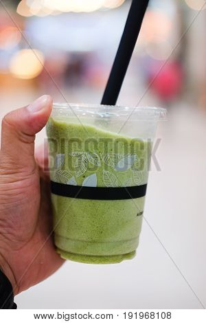 Hand holding cup of Japanese matcha green tea ice smoothie frappe