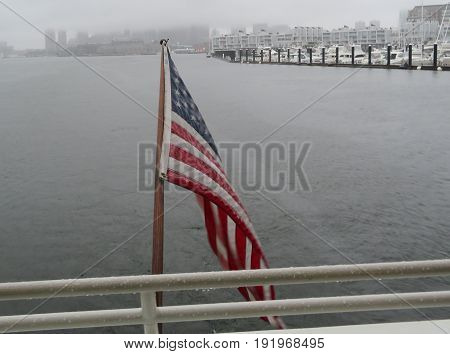 US Flag on boat in Boston Harbor with Foggy background