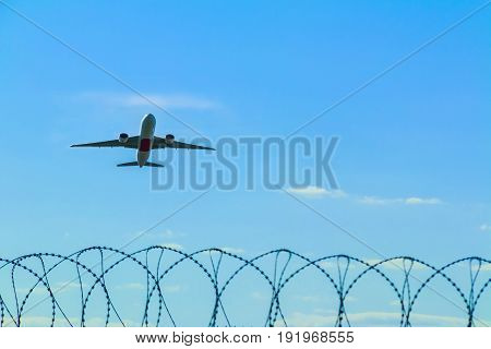 Airliner taking off over a barbed wire fence of the aerodrome
