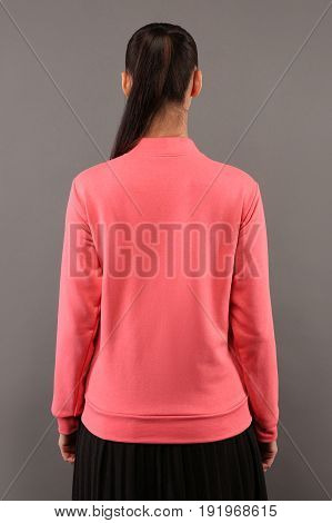 Back of Young hipster girl wearing blank pink cotton zip up sweatshirt with copy space for your design or logo mock-up of ltemplate womens hoodie grey wall in the background
