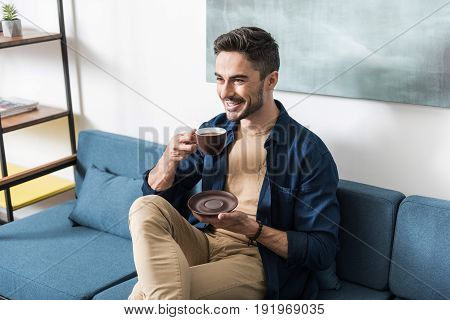 Jolly young bearded man drinking coffee with pleasure in his living room. He is sitting on sofa, holding cup and saucer in hands and smiling