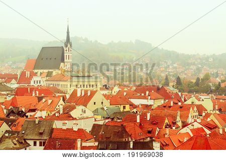 Cesky Krumlov - a famous czech historical beautiful town frome above, travel background with red roofs and chapel