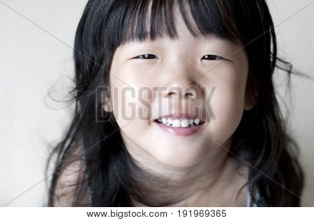 Portrait of single eyelid little Asian girl smiling, looking up.