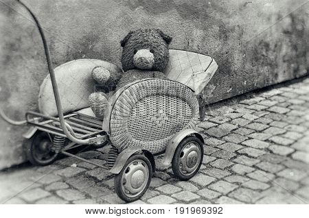 Old dirty Teddy bear toy sitting in the retro baby carriage on the street - lost lonely children concept, vintage hipster grunge image, black and white version