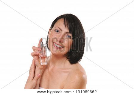 Mature well groomed woman with bottle of perfumes. Portrait of senior woman with bottle of perfume