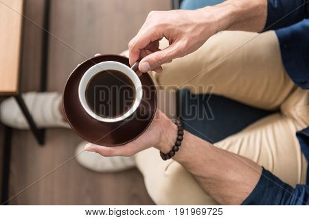 Close up of hands of young man holding cup of coffee with saucer. He is sitting on couch near table in his room. Top view