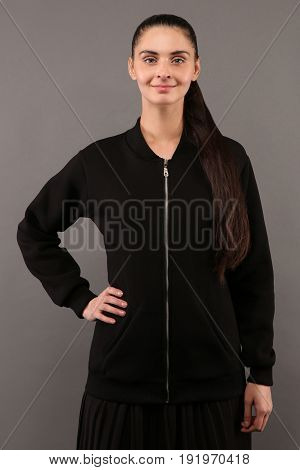 Young hipster girl wearing blank black cotton zip up sweatshirt with copy space for your design or logo mock-up of ltemplate womens hoodie grey wall in the background