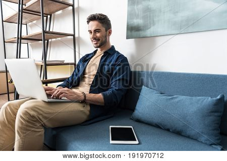 Cheery young bearded man is sitting on his home sofa and working with help of laptop computer. He is typing something and holding gadget on his laps. Copy space in right side