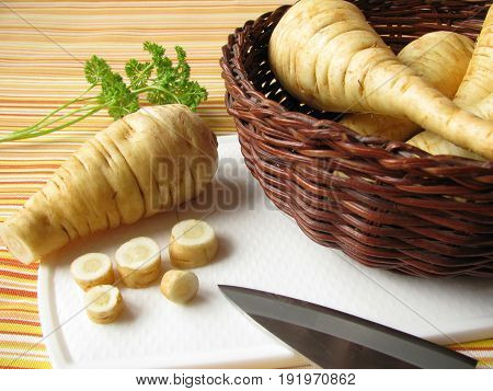 Root vegetables parsnips in basket on cutting bord