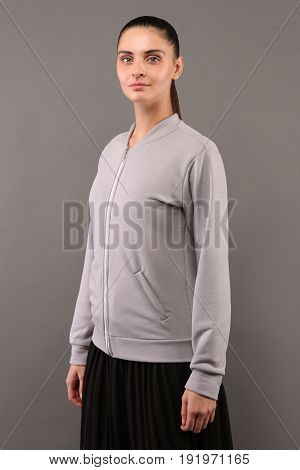 Young hipster girl wearing blank grey cotton zip up sweatshirt with copy space for your design or logo mock-up of ltemplate womens hoodie grey wall in the background